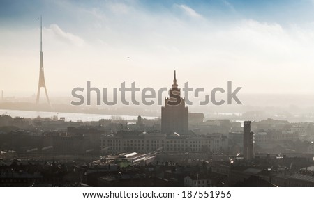 RIGA, LATVIA - DECEMBER 31, 2013: Cityscape panorama of Riga town with tall living house and TV tower in the fog on the coast of Daugava River