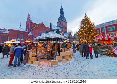 RIGA, LATVIA - DECEMBER 28, 2014: People enjoy Christmas market held at Old Town's Dome Square, Riga, Latvia. Riga is the City where the tradition of decorating the Christmas Tree started - stock photo