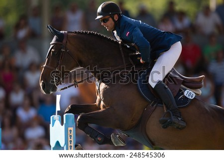 RIGA, LATVIA - JULY 27: Andis Varna with horse Never Mind (22) jumps over obstacle at World Cup qualifying round CSI2*-W/CSIYH1* RIGA-2014 on JULY 27, 2014 in RIGA