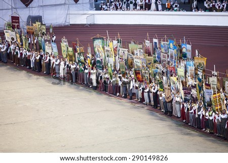 RIGA, LATVIA - JULY 4, 2013: Participants of Grand Dance Performance of the Latvian Nationwide Song and Dance Celebration with  collective flags at Daugava stadium. - stock photo