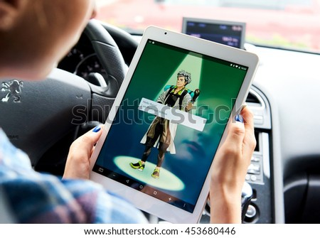 Riga, Latvia- July 17, 2016: Woman sitting in a car and playing a Pokemon Go game. Pokemon Go is a popular virtual reality game for mobile devices