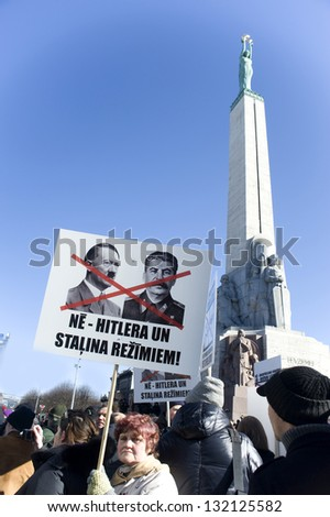 "RIGA, LATVIA-MARCH 16: Antifascists protest against procession of legionaries of ""Waffen SS"" at Freedom monument.  Riga, Day of memory of legionaries of ""Waffen SS"" in March 16, 2013 in Riga. - stock photo"