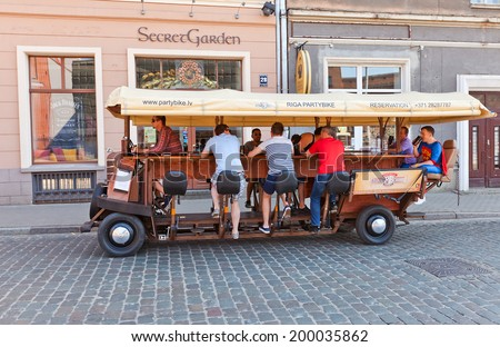 Riga, Latvia - May 25, 2014: Partybus Beer Bike with bar attendants on the street of Riga, Latvia. It is a pedal powered bar on the wheels. As the bar attendants pedal the barman is steering   - stock photo