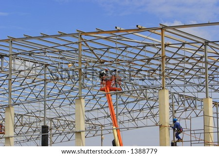 Riggers assembling a steel structure, worker on the left drilling into concrete pillar. - stock photo