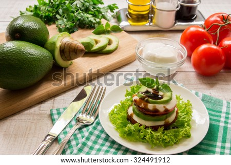 Right a white plate with salad of sliced layers of mozzarella, tomato, avocado and lettuce on background blurred tomatoes, mozzarella, avocado, avocado slices. Vegetarian diet salad and ingredients.