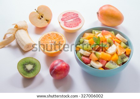 "Right blue plate with fruit salad of orange, grapefruit, kiwi, mango, banana, plum and apple, left spread all ingredients of the salad on white background. Fruit salad ""Energy Charge"" and ingredients."