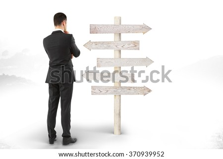 Right decision concept with businessman looks at the pointer with wooden arrows
