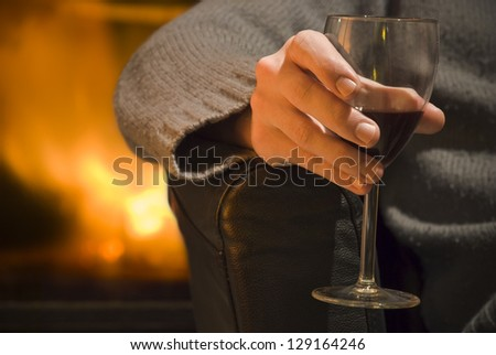 Right hand of a young man holding a glass of wine in front of a fireplace. - stock photo