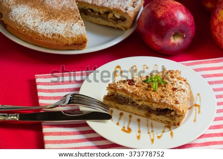 Right plate with a piece of apple pie on a red with white stripes napkin, left fork, knife in the background incised apple pie, red apples. Apple pie with nuts and raisins. Horizontal. Daylight. - stock photo