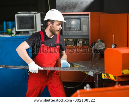 right side view of a worker wearing red overalls, white protective helmet and gloves, standing, handling a sheet of metal plates onto the table of a red-painted heavy-duty machinery - stock photo
