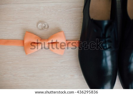 rigs, pink bow tie and black shoes on the floor - stock photo