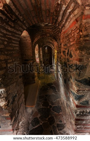 Rila Park, Bulgaria - July 30, 2016: A narrow stone staircase in the tower of a medieval castle ancient Christian monastery of Rila, Bulgaria. Mysterious gloomy tunnel with walls of stone