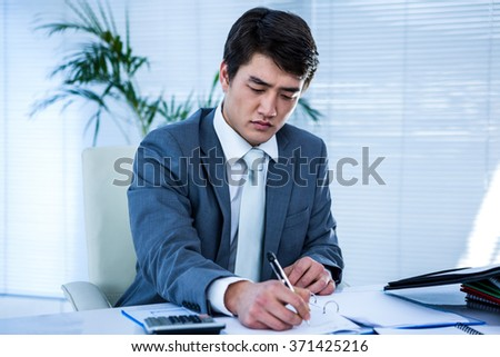 Riled up asian businessman in his desk and writing somethings - stock photo