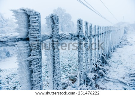 Rime covered fence by the ski-lift closed due to bad weather - stock photo