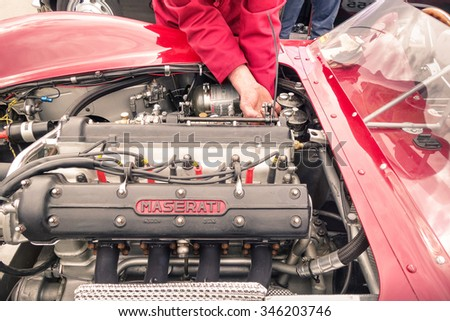 RIMINI, ITALY - MAY 15, 2015: unidentified mechanic works at the engine of vintage Maserati race car on the seafront road on may 15, 2015 in Rimini, Italy - stock photo