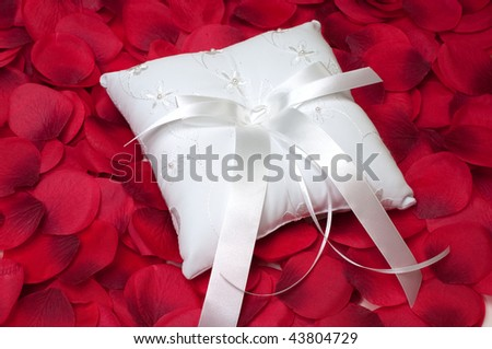 Ring bearer's pillow on bed of red rose petals. - stock photo