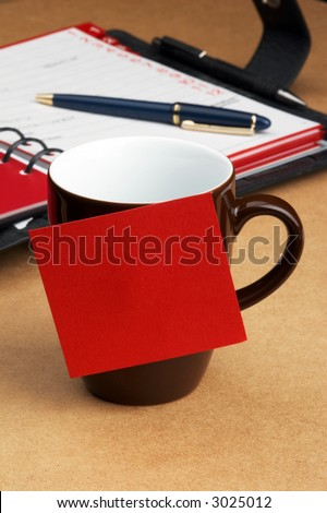 Ring binder and brown Cup of coffee on desk with a red post-it on it for further use - stock photo