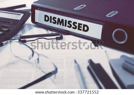 Ring Binder with inscription Dismissed on Background of Working Table with Office Supplies, Glasses, Reports. Toned Illustration. Business Concept on Blurred Background. - stock photo