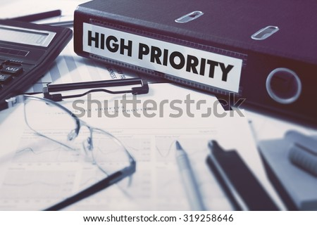 Ring Binder with inscription High Priority on Background of Working Table with Office Supplies, Glasses, Reports. Toned Illustration. Business Concept on Blurred Background. - stock photo