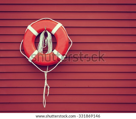 Ring buoy hanging against red, wooden wall background, copy space. Vintage filter effects. - stock photo