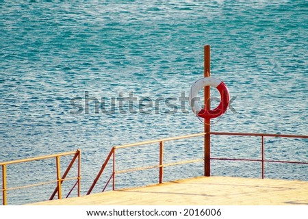 Ring-buoy on a wooden skeleton pier - stock photo