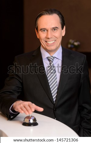 Ringing at the service bell. Mature businessman ringing at the service bell while standing on the hotel reception - stock photo