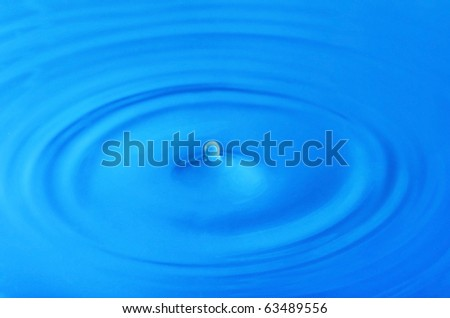 Rings and drop on the blue water - stock photo
