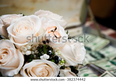 rings lie on a wedding bouquet from roses - stock photo