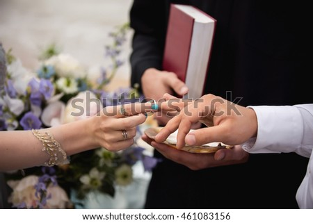 Rings. Wedding rings. Hands of bride and groom in solemn process of exchanging rings, symbolizing the creation of new happy family. Bride putting a ring on groom's finger during wedding ceremony