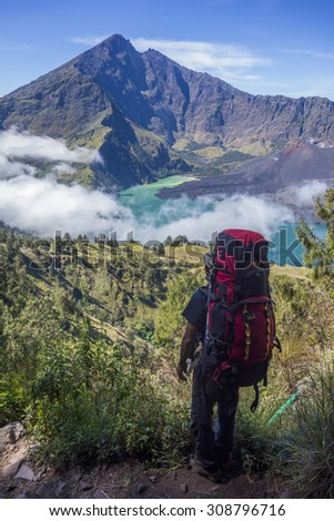 RINJANI MOUNTAIN, LOMBOK, INDONESIA-JUNE 11,2015: Mountain guide AB Pramono with trekking pole looks-on  on the way to Rinjani Mountain in Lombok, Indonesia. - stock photo