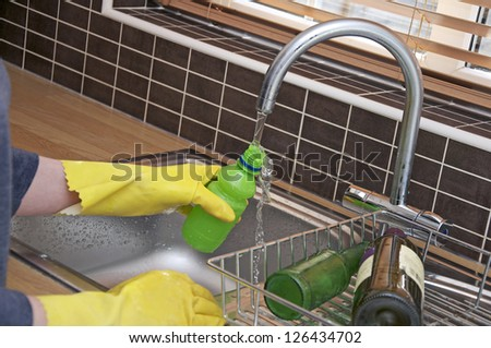 Rinsing plastic bottle in kitchen sink for recycling - stock photo