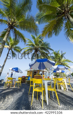 RIO DE JANEIRO - APRIL 4, 2016: A kiosk selling drinks and coconuts sits between palm trees at the Arpoador end of Ipanema Beach.