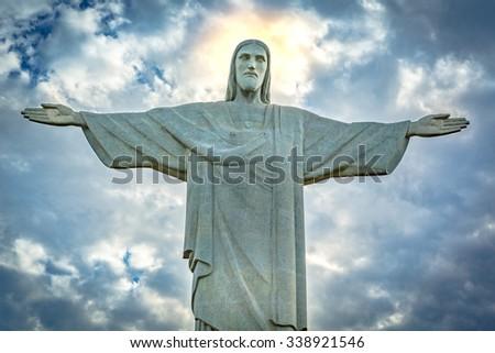 RIO DE JANEIRO - AUGUST 19, 2015: Statue of Christ the Redeemer under a dramatic sunset sky. Christ the Redeemer is an Art Deco statue created by French sculptor Paul Landowski - stock photo