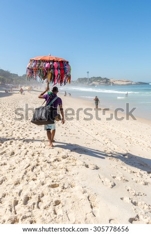 RIO DE JANEIRO, BRAZIL - AUGUST 13, 2015: A beach vendor selling sun hats and selfie sticks carries his merchandise along Ipanema Beach.
