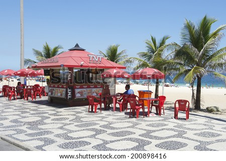 RIO DE JANEIRO, BRAZIL - FEBRUARY 05, 2014: Customers relax at a red kiosk with matching chairs and umbrellas on the boardwalk at Ipanema Beach.