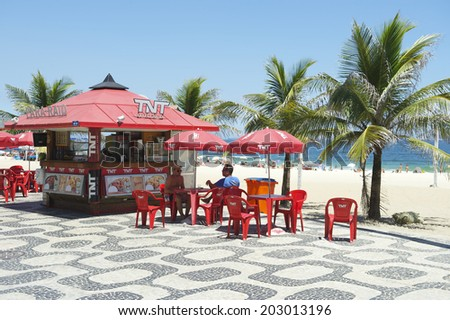 RIO DE JANEIRO, BRAZIL - FEBRUARY 05, 2014: Palm trees decorate the view from a red kiosk with matching chairs and umbrellas on the boardwalk at Ipanema Beach.
