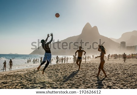 RIO DE JANEIRO, BRAZIL - FEBRUARY 24: Unidentified people playing football kicking soccer balls at sunset Ipanema Beach, February 24, 2013 in Rio de Janeiro, Brazil - stock photo