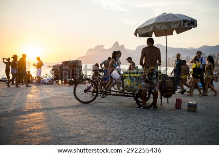 RIO DE JANEIRO, BRAZIL - FEBRUARY 21, 2015: Vendors and tourists gather at Arpoador for the daily sunset watching ritual. - stock photo