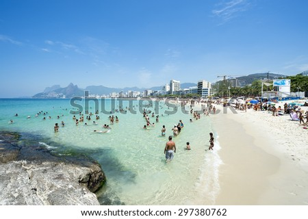 RIO DE JANEIRO, BRAZIL - JANUARY 17, 2015: Beachgoers take advantage of calm seas at the Arpoador end of Ipanema Beach against a city skyline with Two Brothers Mountain.