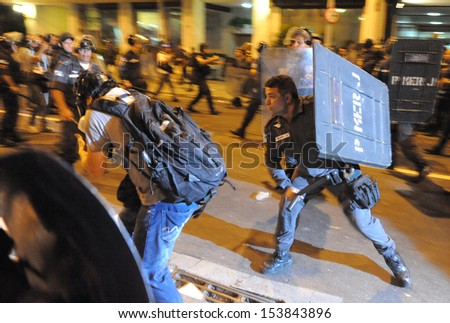 RIO DE JANEIRO,BRAZIL - JULY 23, 2013: Anti- riot police  hits a press photographer during a protest against the Rio's governor during the Pope Francisco visit on 23/07/2013, in Rio de Janeiro, Brazil. - stock photo