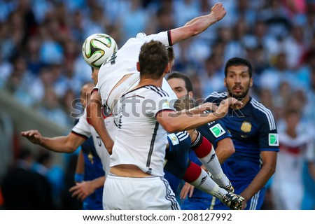 RIO DE JANEIRO, BRAZIL - July 13, 2014: Howedes of Germany competes for the ball during the World Cup Final game between Argentina and Germany at Maracana Stadium. NO USE IN BRAZIL.