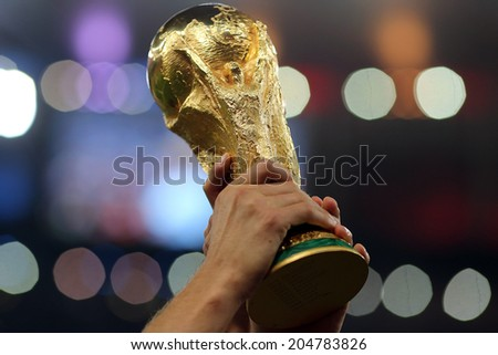 RIO DE JANEIRO, BRAZIL - July 13, 2014: The World Cup Trophy is lifted during celebrations after the 2014 World Cup Final game between Argentina and Germany at Maracana Stadium. NO USE IN BRAZIL. - stock photo