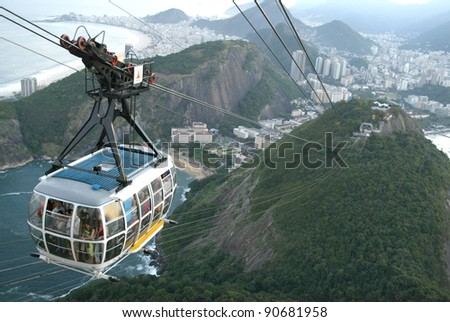 RIO DE JANEIRO, BRAZIL - JULY 16:  Tourists ride a cable car as it ascends up the summit of Sugar Loaf Mountain July 16, 2005 in Rio de Janeiro, Brazil. - stock photo