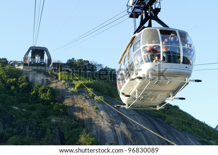 RIO DE JANEIRO, BRAZIL - JULY 16:  Tourists ride a cable car as it descends from the summit of Sugar Loaf mountain July 16, 2005 in Rio de Janeiro, Brazil. - stock photo
