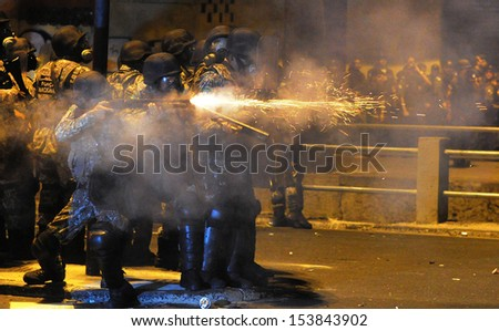RIO DE JANEIRO,BRAZIL - JUNE 30, 2013: police fires tear gas bombs on demonstrators  during a protest at Maracana stadium on the Confederation Cup final match, on 06/30/2013 in Rio de Janeiro, Brazil. - stock photo