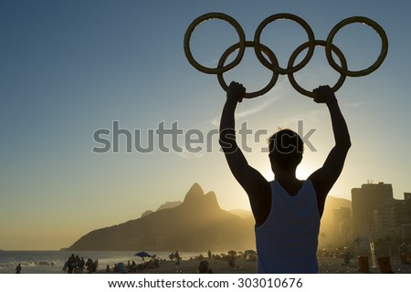 RIO DE JANEIRO, BRAZIL - MARCH 05, 2015: Athlete holding Olympic rings above sunset city skyline view of Two Brothers Mountain at Ipanema Beach. - stock photo