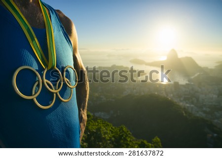 RIO DE JANEIRO, BRAZIL - MARCH 05, 2015: Athlete wearing Olympic rings gold medal above city skyline view of Sugarloaf Mountain and Guanabara Bay at sunrise. - stock photo
