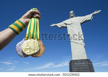 RIO DE JANEIRO, BRAZIL - MARCH, 2015: Hand holds gold, silver and bronze medals hanging from Brazil color ribbons in clear blue sky at the statue of Christ the Redeemer. - stock photo