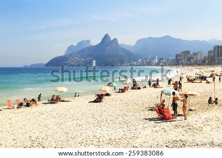 Rio de Janeiro, Brazil -?? May, 5 2014:  Tourists and locals enjoying themselves at Ipanema Beach on a beautiful summer day. This view is towards the west with Two Brothers Mountain in the background. - stock photo
