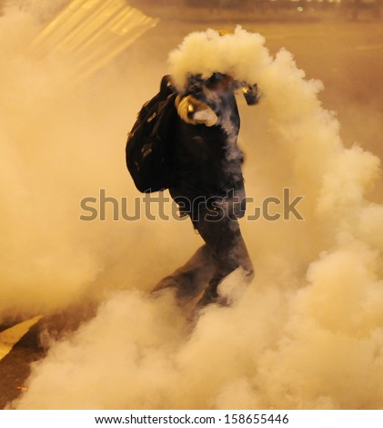 RIO DE JANEIRO, BRAZIL - OCTOBER 15: a demonstrator throws back at the police a tear gas bomb, along the city center main avenue, Rio Branco, during demonstrations in support to the teacher's strike as the annual October 15 Teachers' Day holiday came to a - stock photo